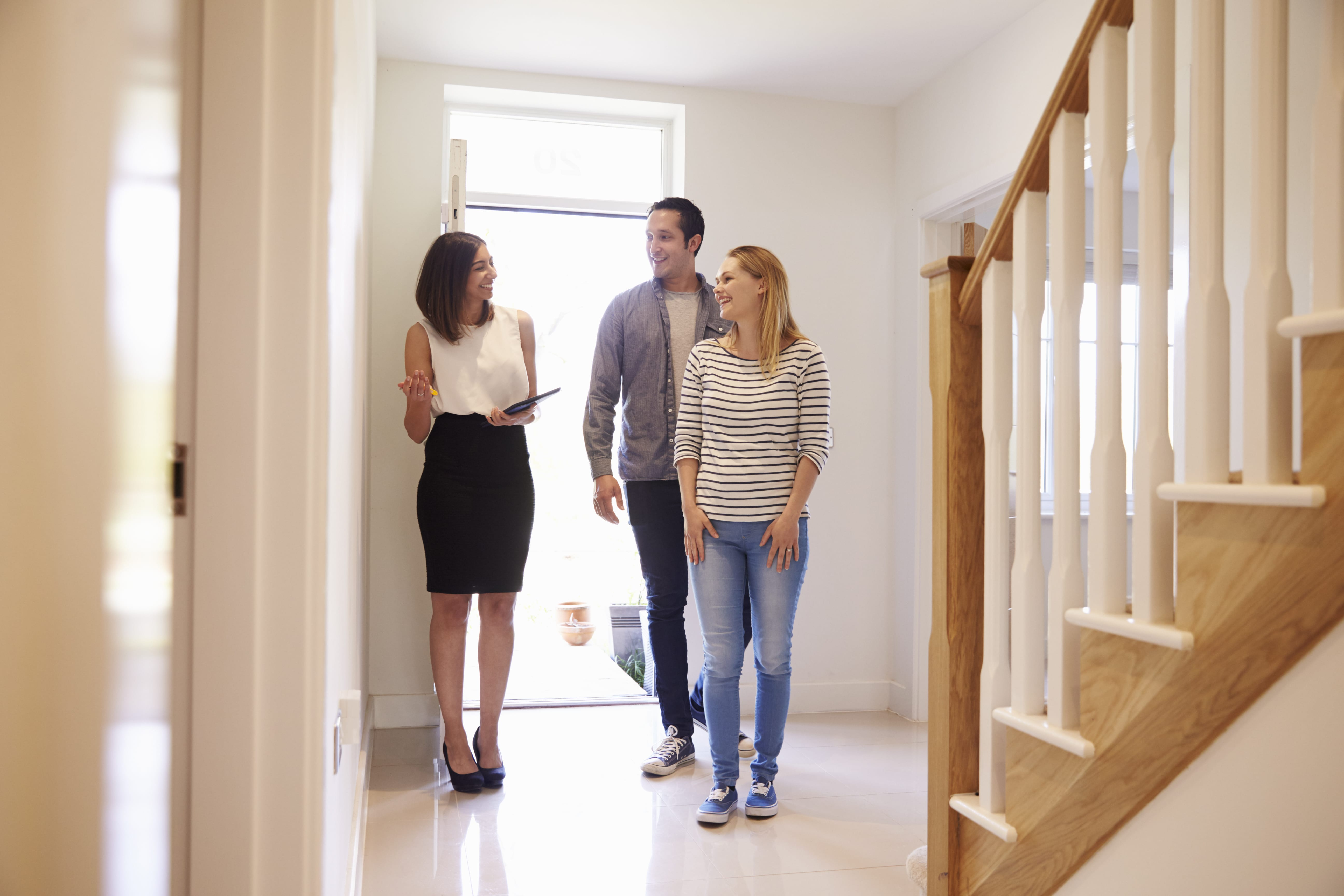 realtor-showing-young-couple-around-property-for-PRUUFP3-min